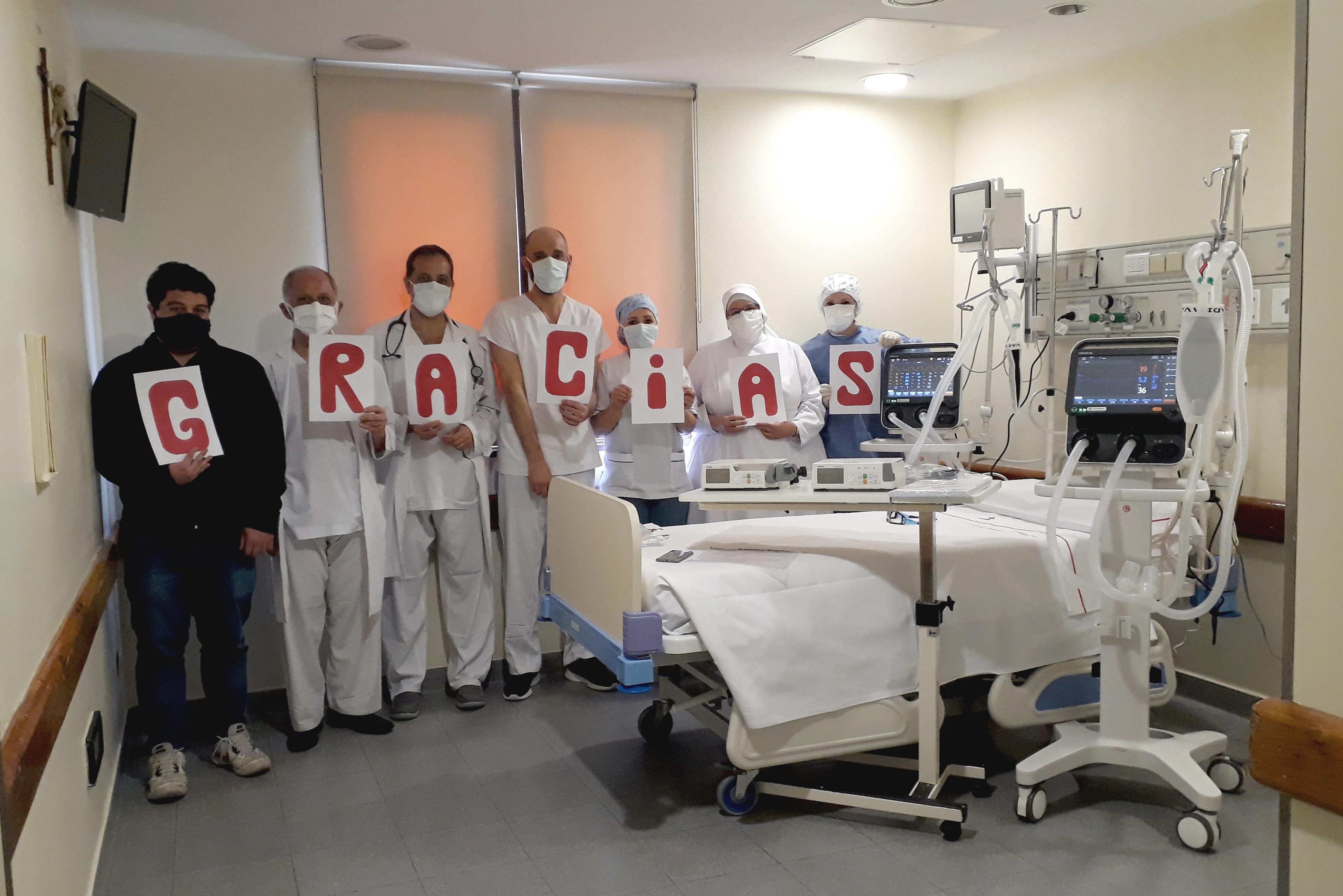 Personal de la Clínica San Camilo en habitación de terapia intensiva mostrando cartel de gracias junto a los dos nuevos respiradores